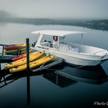 Boat and kayaks on Thesen Island in Knysna Lagoon on a misty morning.